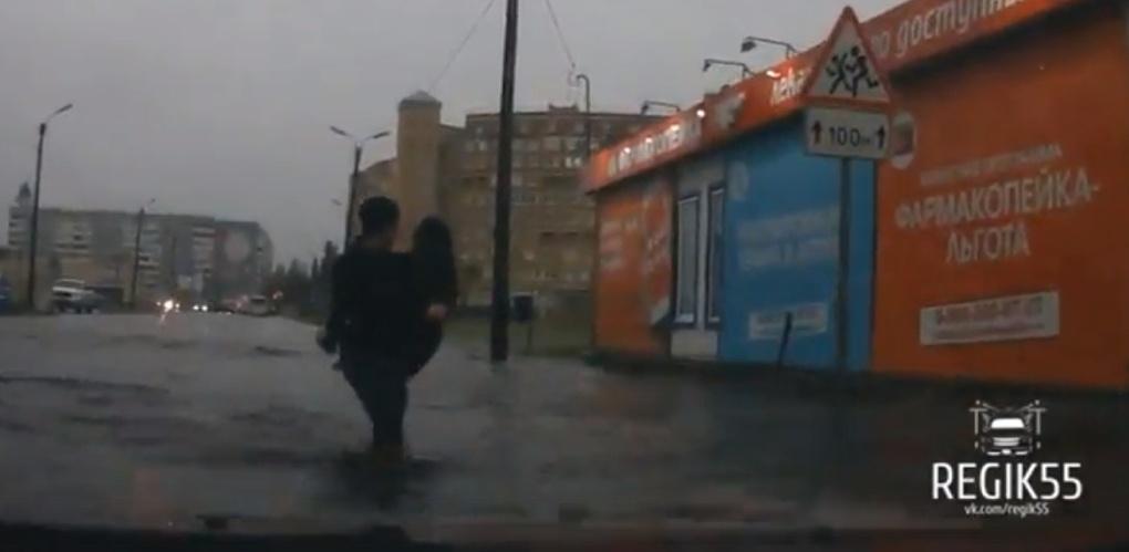 Омич в ливень по-рыцарски переносил дам через затопленную дорогу